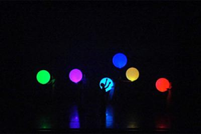 Dancers interact with illuminated inflatable balls